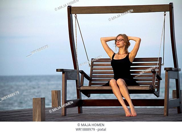 Young woman in sundress relaxes on a swing, hands behind head, Lankayan Island, Borneo, Malaysia