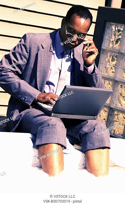 Businessman on laptop by hot tub