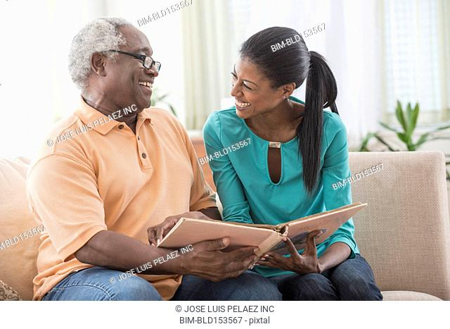 Father and daughter looking at photo album in living room