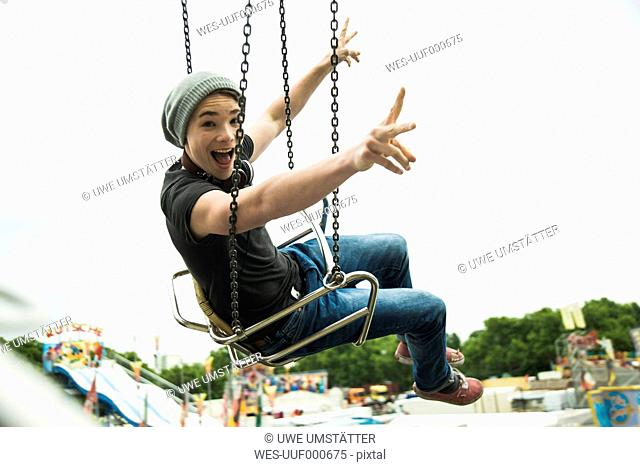 Teenage boy on chairoplane at fun fair