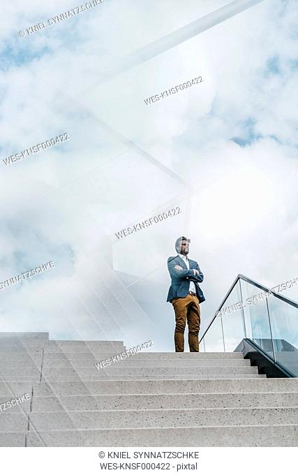 Businessman standing atop of stairs