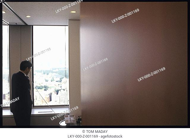 Business man on telephone looks out office window at city below