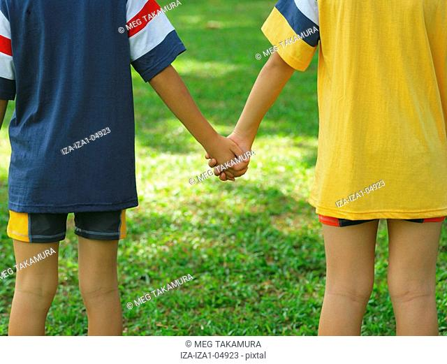 Mid section view of two boys holding hands