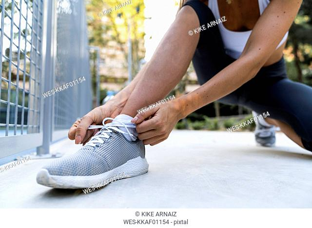 Close-up of sportive woman tying her shoes before workout