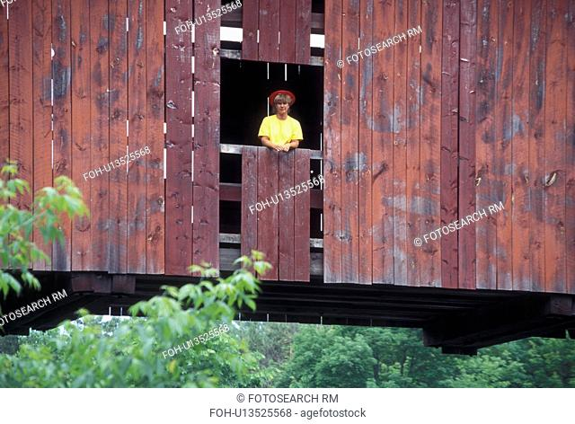 covered bridge, spring, Northfield Falls, VT, Vermont, Woman stands in window of Slaughter House Covered Bridge in the spring in Northfield Falls