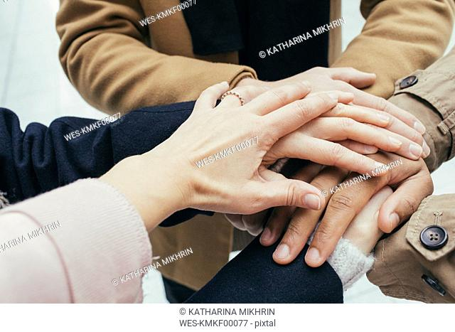 Group of friends putting hands together