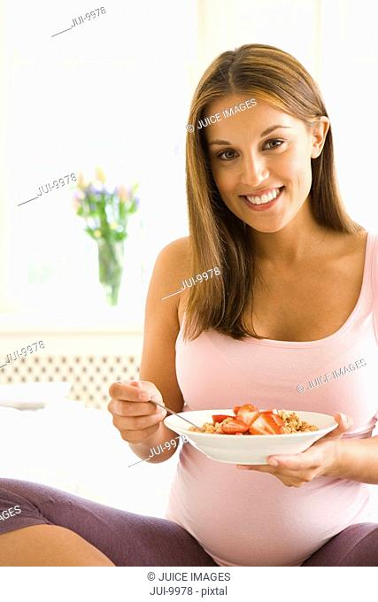 Young pregnant woman eating breakfast, smiling, portrait, close-up