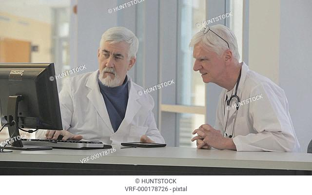 Two doctors discussing patient data on computer and tablet, one doctor with Muscular Dystrophy