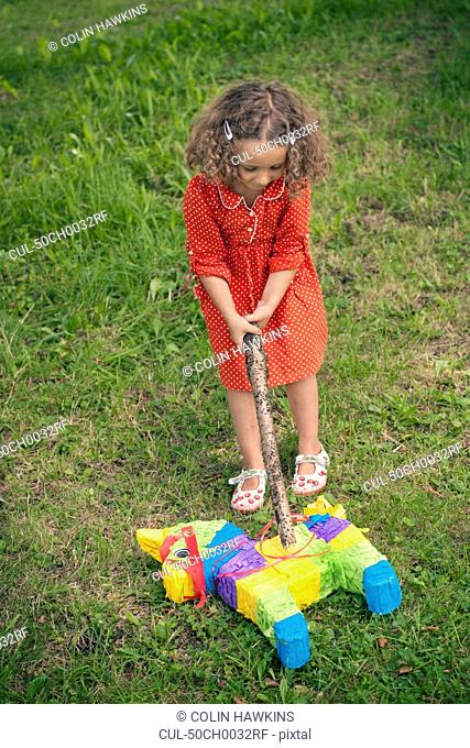 Girl opening pinata on ground at party
