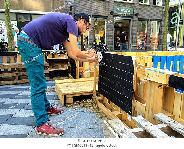 Tilburg, Netherlands. Young male urban farmer painting a message on the fence of his urban kitchen garden