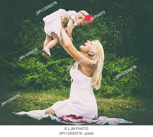A beautiful young mother with long blonde hair enjoying quality time with her cute baby daughter and tossing her in the air while sitting on the grass in a city...