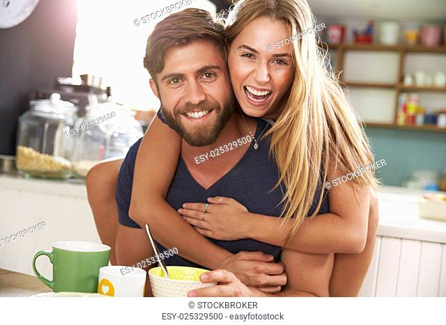 Young Couple Eating Breakfast In Kitchen Together