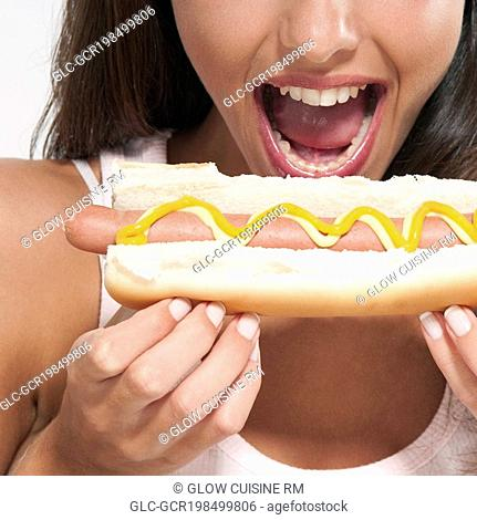 Close-up of a woman eating a hot dog