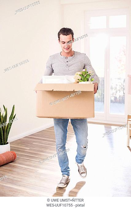 Young man carrying cardboard box in new home