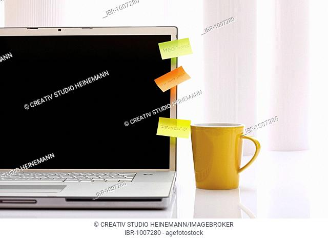 Colourful notepads on laptop and yellow coffee cup