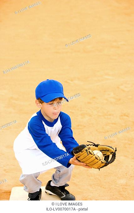 Young boy catching baseball