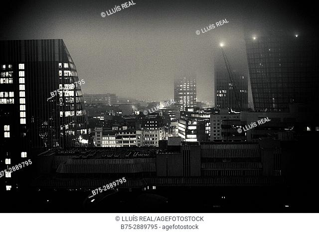 Office and residential buildings at dusk with fog and lights. Bankside, London, England