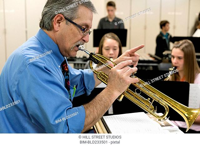 Caucasian teacher playing trumpet in music class