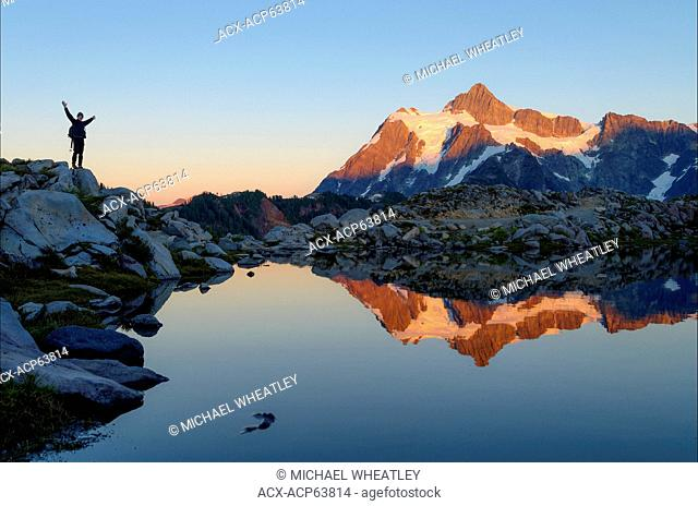 Jubilant hiker and reflection of Mount Shuksan in alpine tarn, Mount Baker-Snoqualmie National Forest, Washington, United States of America