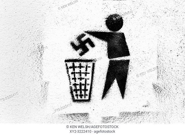 Anti-Nazi graffiti. Swastika being thrown into rubbish bin. Photographed in Tarifa, Spain