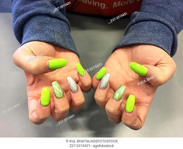A woman shows off brightly coloured neon nails on two hands, Ontario, Canada. The nails have to be repainted once every two weeks