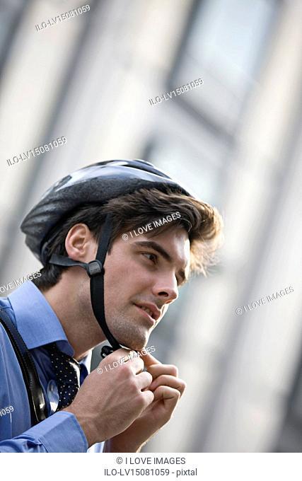 A businessman putting on a cycling helmet