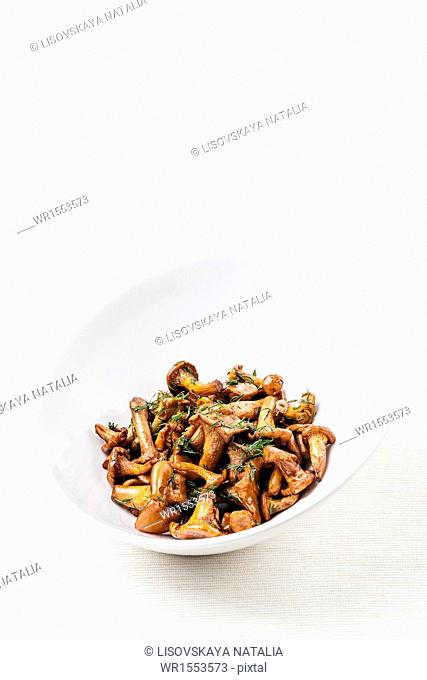 Fried wild mushrooms in white bowl