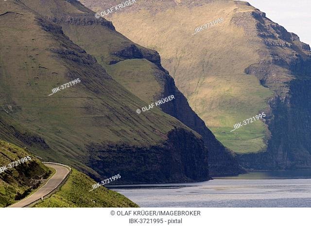 Road and mountains towering from the sea, Kalsoy, Norðoyar, Faroe Islands, Denmark
