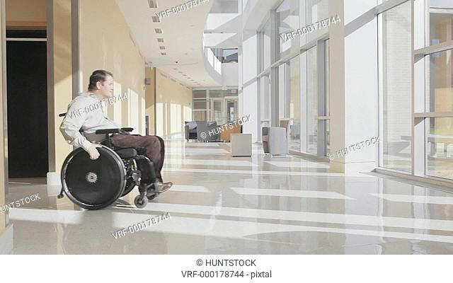 Man with spinal cord injury in wheelchair demonstrating use of wheelchair in office building