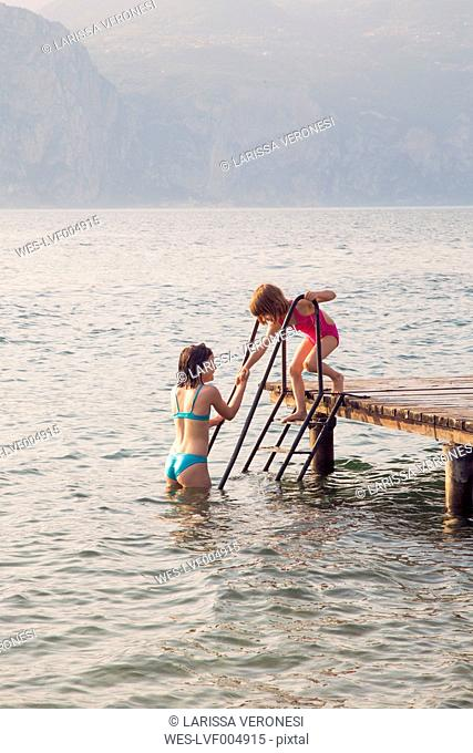 Italy, Brenzone, girl helping her little sister from jetty into the lake