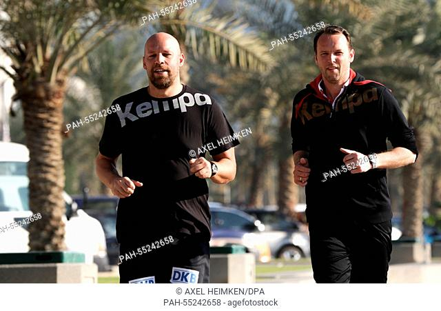 Germany's headcoach Dagur Sigurdsson (r) and Germany's assistant coach Axel Kromer are jogging along the skyline of Doha during the men's Handball World...