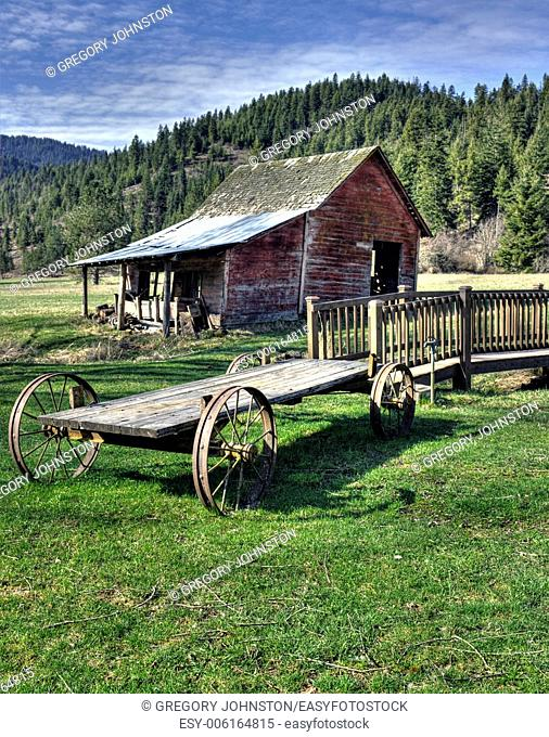 An old wagon sits near a small bridge and a small barn in north Idaho