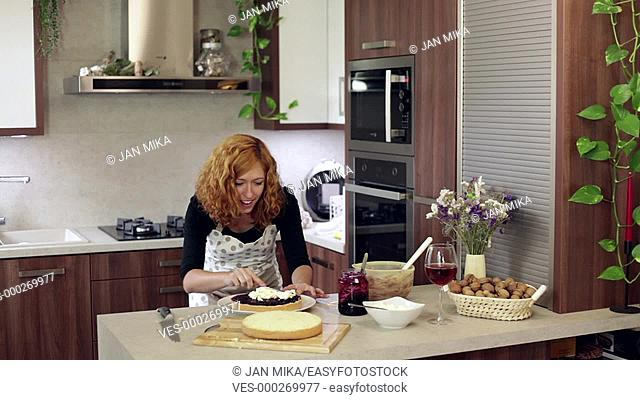 Young happy woman spreading a cream on homemade cake in the kitchen at home
