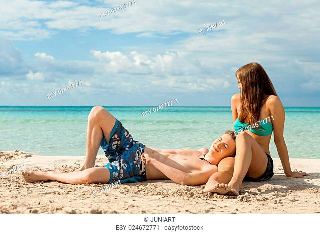 Happy attractive affectionate young couple sunbathing together on the beach in their swimwear while enjoying a tropical summer holiday during the annual...