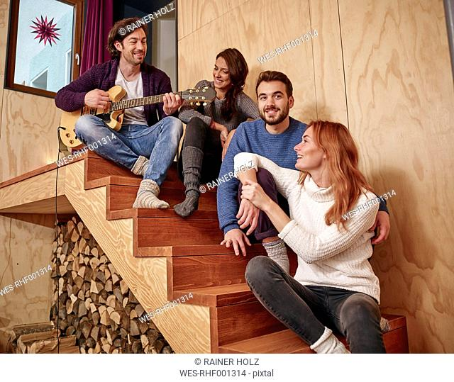 Friends sitting on wooden stairs playing guitar