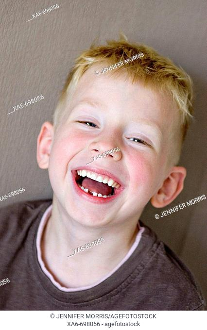 A five-year-old blonde, blue-eyed boy is laughing, showing a gap where he has lost a tooth. He is wearing a brown t-shirt and is standing in front of a brown...