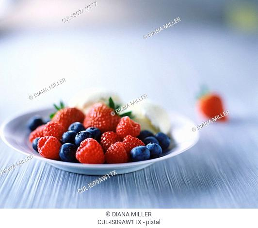 Raspberries, strawberries, blueberries and ice cream in bowl