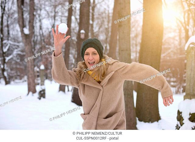 Woman throwing snowball in forest