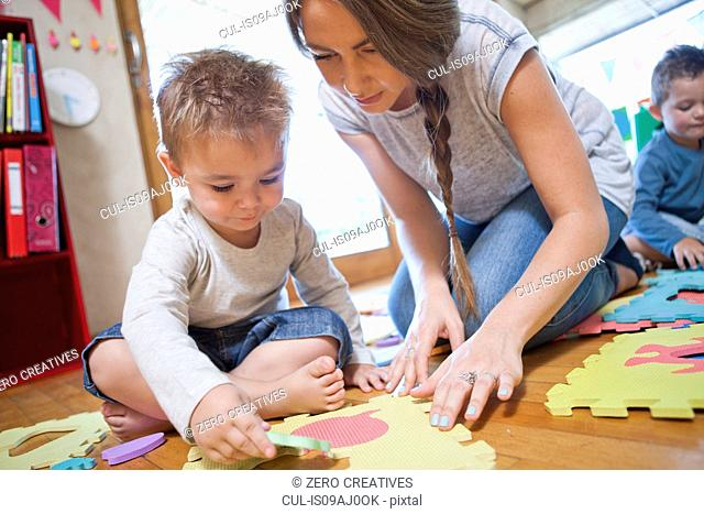 Teacher and boy working with puzzle at nursery school