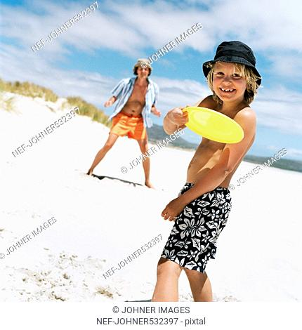 Father and son playing with flying disc on beach, Sweden