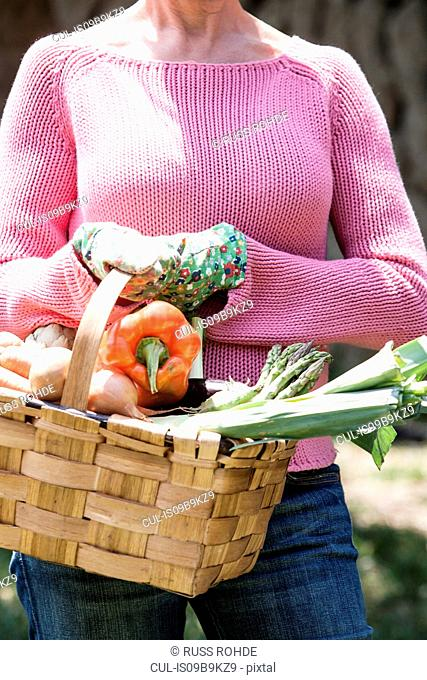Woman with basket of homegrown vegetables