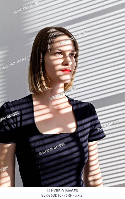 Woman standing in shadow of blinds