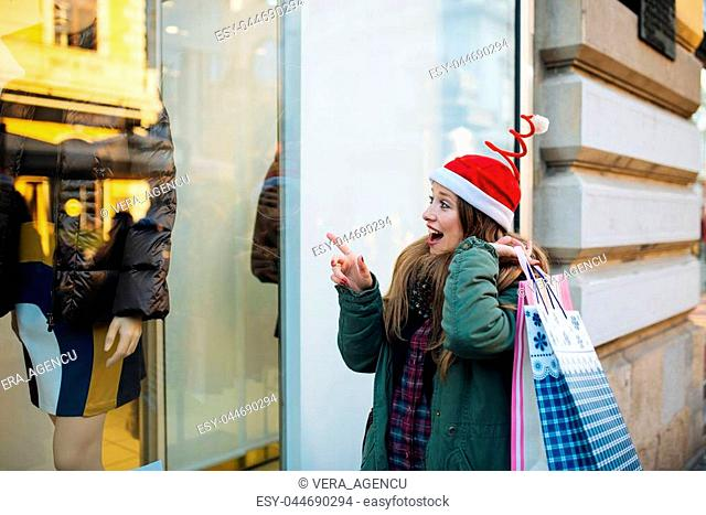Young attractive woman with santa claus hat in front of shopping window looking to buy something