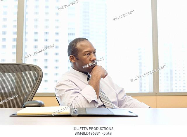 Serious black businessman sitting in conference room