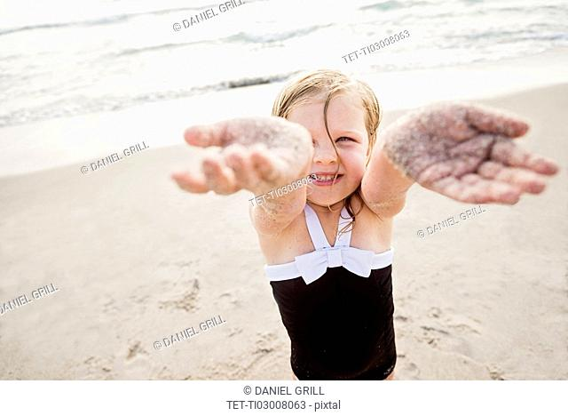 Girl (4-5) standing on beach showing her dirty hands