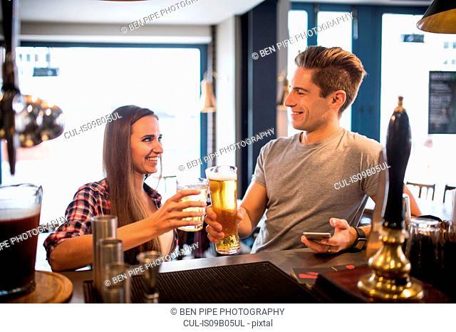 Young couple raising a toast at city bar