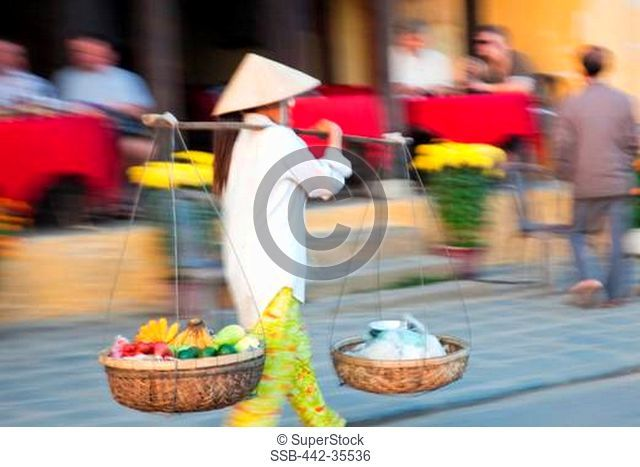 Woman selling fruits in a street, Hoi An, Vietnam
