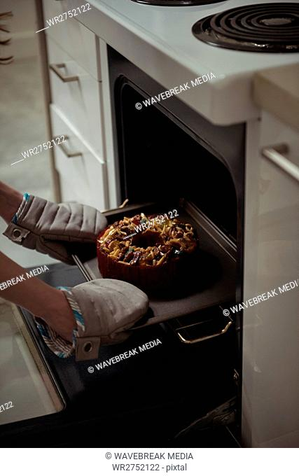 Woman removing baked cake from oven