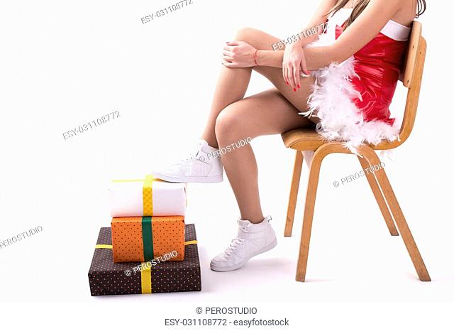 Christmas girl on a wooden chair and gifts on white background