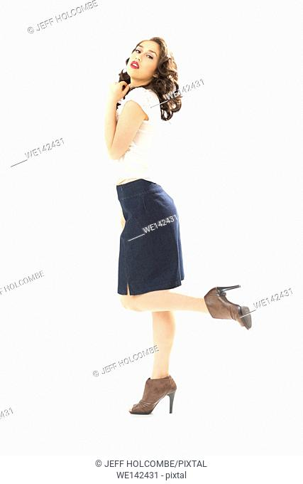 Beautiful young woman in white blouse and blue denim skirt, full length profile, in brown heels, hand on neck, head turned back